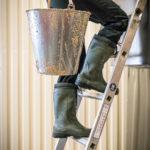 Yuval Königstein trägt eimerweise den Sesam die Leiter hoch zur Schälmaschine.