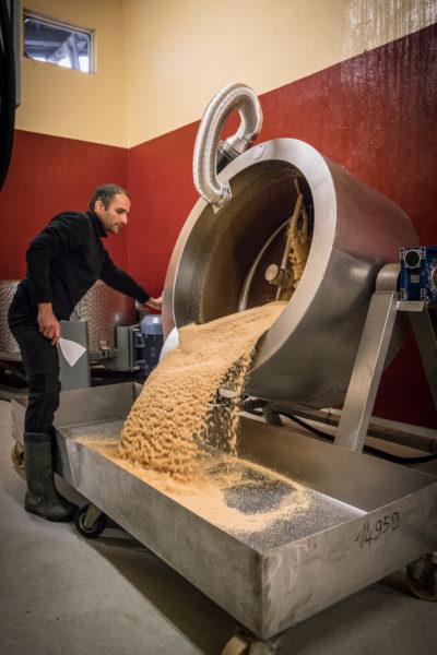 Yuval Königstein kippt den gerösteten Sesam in die große Edelstahlwanne zum Auskühlen.