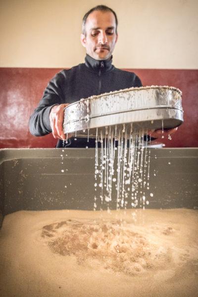 Der im Salzwasser oben auf schwimmende Sesamöl wird mit einem Sieb abgeschöpft.