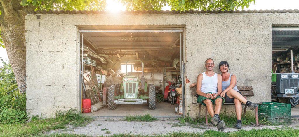 Martina und Manfred vor der Garage ihrer Gärtnerei auf dem Gartenbänkchen sitzend