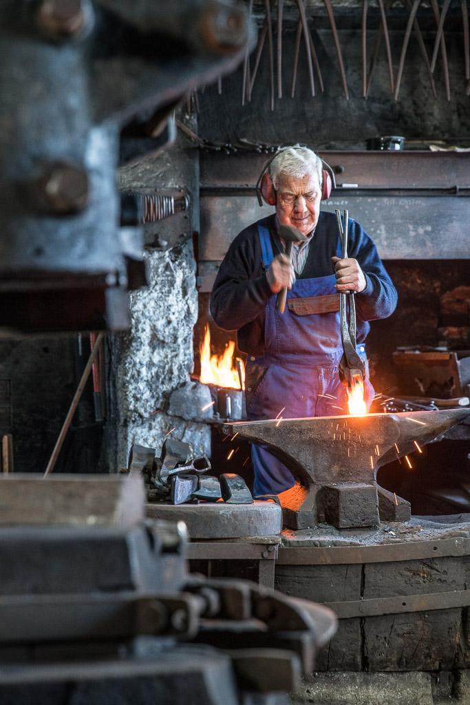Josef Geisler bearbeitet mit dem Schmiedehammer den glühenden Sapie auf dem Amboss.