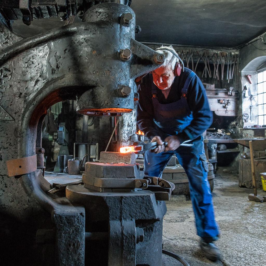 Josef Geisler bearbeitet mit dem riesigen Schmiedehammer einen glühenden Axtblattrohling.
