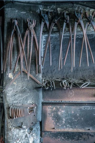 Schmiedezangen, aufgereiht an der Wand entlang, oberhalb der Esse.
