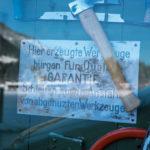 Ausgestellte Werkzeuge und ein Schild: Hier erzeugte Werkzeuge bürgen für Qualität. Garantie. Schleifen sowie Anstählen von abgenutzten Werkzeugen.