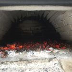 Glühende Kohlen im Holzbackofen
